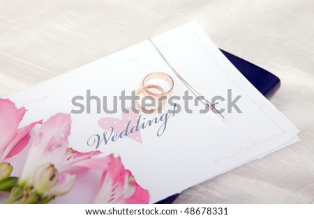 Pair of wedding rings on a bible with cross and flower