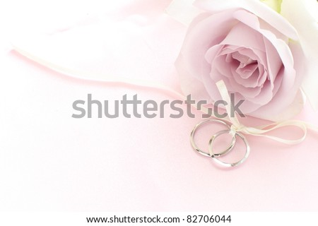 pair of wedding rings with pastel purple rose for background image