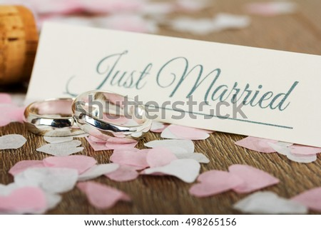 pair of white gold wedding rings on a wooden background with confetti