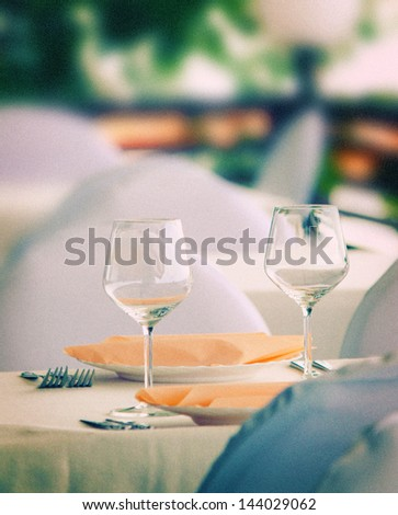 Pair of wineglasses on elegant table setting. Outdoor shot. Toned image, grain added - stock photo