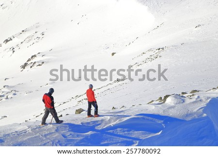 Pair of winter hikers isolated on snow covered mountain ridge - stock photo