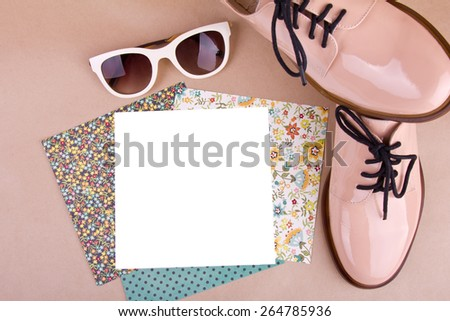 pair of woman's lacquered shoes, sunglasses, a set of pattern paper on beige background - stock photo