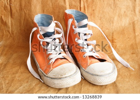Pair of womens used orange  trainers and laces - stock photo