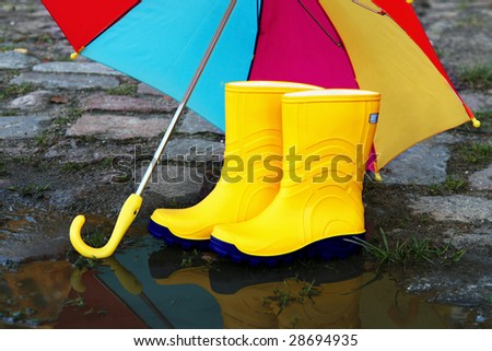 Pair of yellow rubber boots with an open umbrella beside a puddle - stock photo