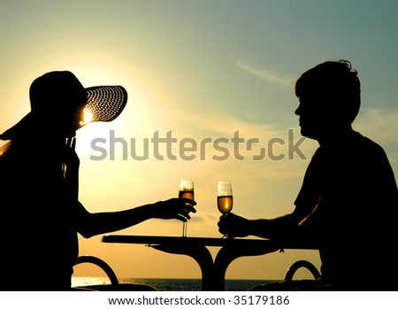 Pair silhouette sit at a table and hold goblet with wine on sundown