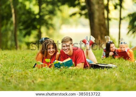 pair successful students with a textbook in a Park on a Sunny da - stock photo