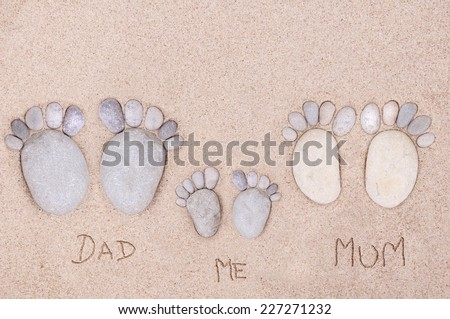 pairs feet (family)  made of a stone on the sea sand  - stock photo