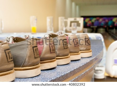 Pairs of bowling shoes lined up in shoe rack - stock photo