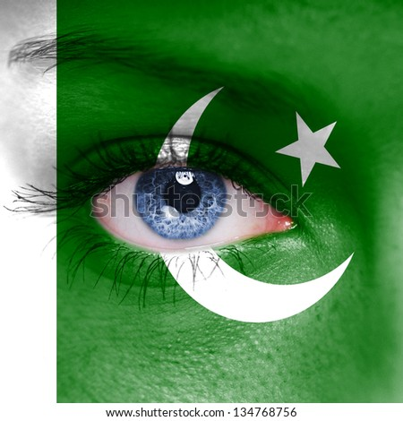 Pakistan flag painted on woman face - stock photo