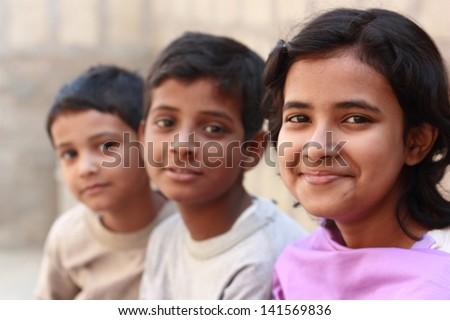 Pakistani siblings making pose and smile - stock photo