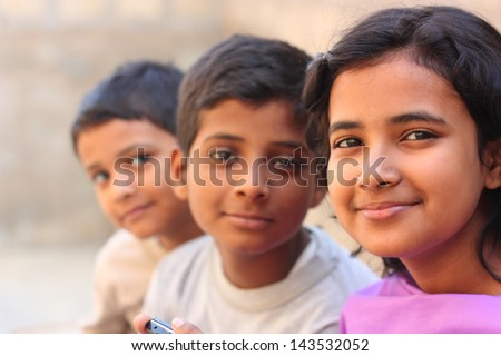 Pakistani siblings making pose and smile - stock photo