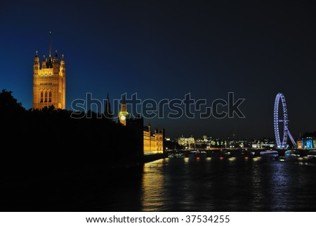 Palace of Westminster and the River Thames, London, England, UK, Europe, at night.  The London Eye is on the right hand side. - stock photo