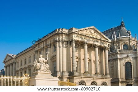 Palace with columns and statue in Versailles over blue sky. France