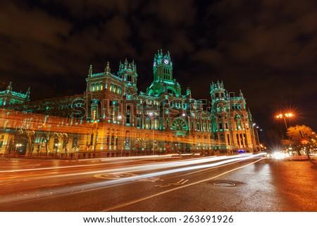 Palacio de Cibeles at the Plaza de Cibeles with light trails of the traffic at night, Madrid, Spain - stock photo