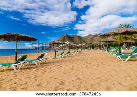 Palapa and chaise-longue on golden sand of Playa de las Teresitas, Tenerife, Spain - stock photo