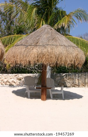 Palapa Hut on the beach with abandoned chairs. - stock photo