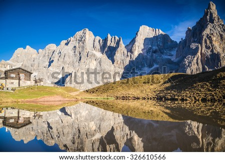 Pale di San Martino Group, Trentino Alto Adige, Italy. The Pale di San Martino Group reflecting itself on a lake during sunset. - stock photo