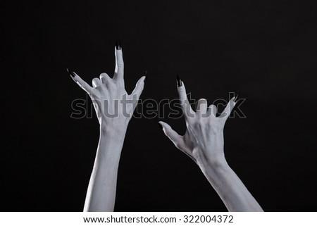 Pale monster hands showing heavy metal symbol, studio shot for Halloween  - stock photo