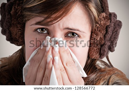 Pale sick woman with a flu, sneezing, in a dark background - stock photo