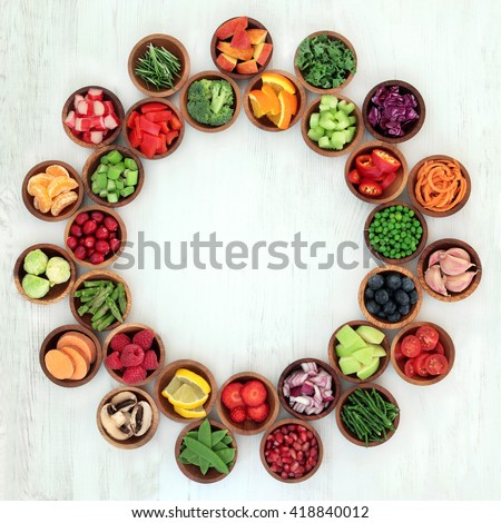 Paleo diet health and super food of fruit and vegetables in wooden bowls forming an abstract wheel over distressed white wood background. High in vitamins, antioxidants, minerals and anthocyanins. - stock photo