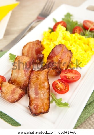 Paleo Style Breakfast of Bacon, Scrambled Eggs, Tomatoes and Arugula Salad - stock photo