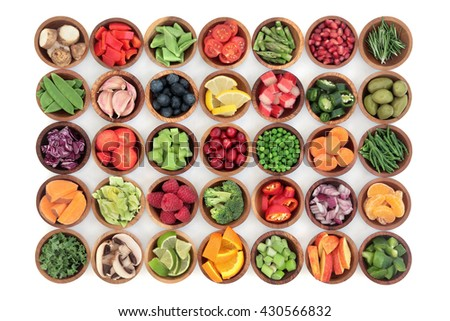 Paleolithic super health food of fruit and vegetables in wooden bowls over white wood background. High in vitamins, antioxidants, minerals and anthocyanins. - stock photo