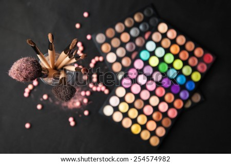 Palette of eyeshadows with set of brushes isolated on black background. Top view. - stock photo