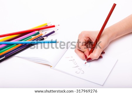 Palette set of colorful sharp pencils brown red yellow blue green violet pink purple lilac and orange colors lying near drawing human hand on paper sheet on white background, horizontal picture - stock photo