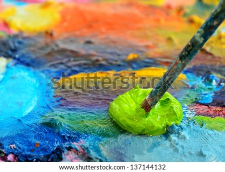 Palette with paint and paintbrush, shallow depth of field. - stock photo