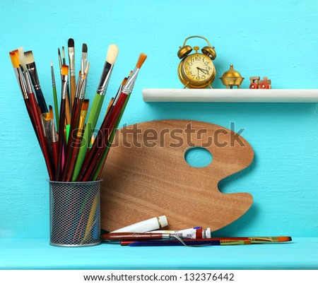Palette with paintbrushes and a paint on a blue background - stock photo