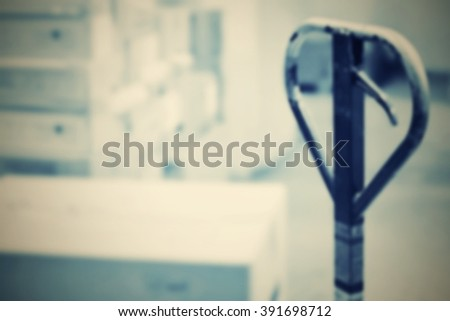 Pallet truck. Abstract blurry warehouse storing. Interior warehouse with boxes and blurred background. - stock photo