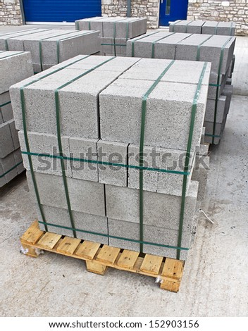 Pallets of breeze blocks at a construction site from a builders merchant known as cinder blocks in the us or Concrete masonry units - stock photo