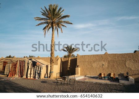 Palm tree and tents by a wall, Merzouga, Morocco