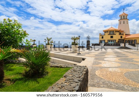 Palm tree garden promenade sea view lighthouse building, Madeira island, Portugal - stock photo