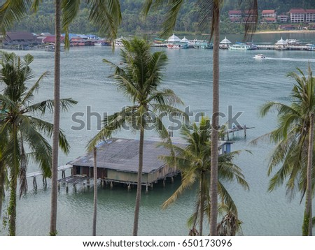 Palm trees and hut at the ocean on the tropical island of Ko Chang in Thailand