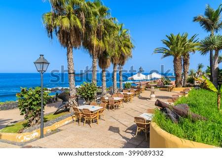 Palm trees and restaurant tables on coastal promenade in Puerto de la Cruz town, Tenerife, Canary Islands, Spain - stock photo