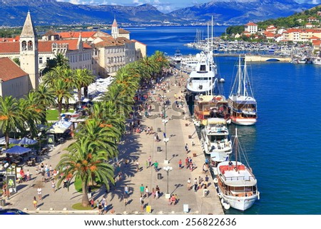 Palm trees and traditional buildings near the pier of old Venetian town, Trogir, Croatia - stock photo