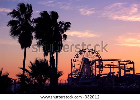 Palm trees, ferris wheel, and roller coaster at sunset