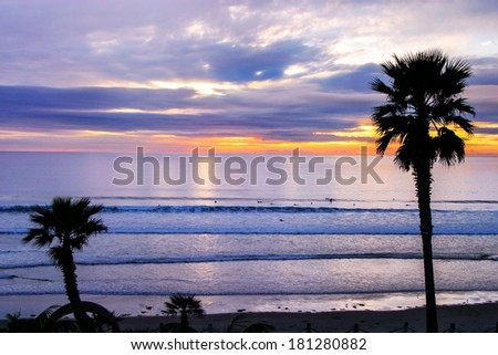 Palm Trees Frame The Lazy Surf Of The Pacific Ocean At Sunset Near San Diego California, USA - stock photo