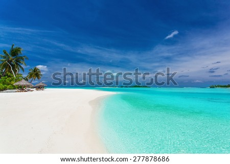 Palm trees over stunning lagoon and white white sandy beach - stock photo