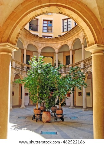 Palma de Majorca, Spain - June 25, 2008: Typical patio in the historic city of Palma, stone arch and green plants in center
