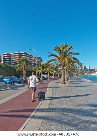 PALMA, MALLORCA, SPAIN - SEPTEMBER 6, 2016: Paseo Maritimo man pushes suitcase on the boardwalk and bicycle track on a sunny day on September 6, 2016 in Palma, Mallorca, Spain.