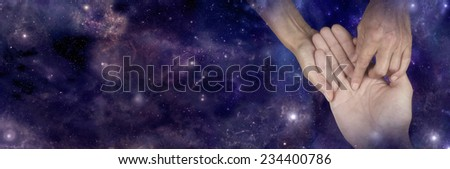 Palmist holding client's hand pointing at heart line giving a palm reading on a wide deep space background with plenty of copy space - stock photo