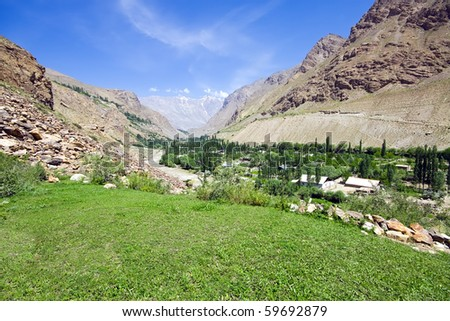 Pamir mountain green meadow and rapid river under blue sky - stock photo