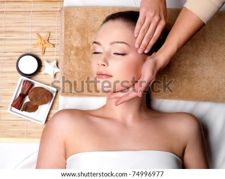 Pampering and massage for beautiful face of young woman in spa salon - indoors - stock photo