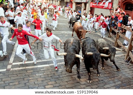 PAMPLONA, SPAIN -JULY 14: Unidentified men run from bulls in street Estafeta during San Fermin festival in Pamplona, Spain on July 14, 2013. - stock photo