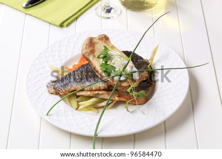 Pan fried fish fillets with baked potato and sauteed vegetable  - stock photo