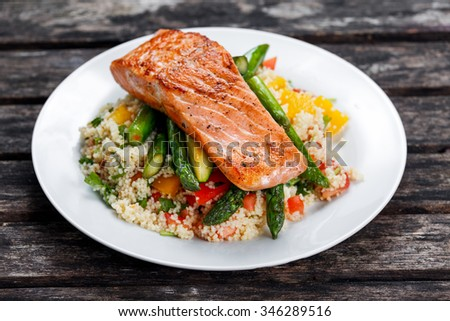 Pan fried salmon with tender asparagus and courgette served on couscous mixed with sweet tomato, yellow pepper salsa - stock photo