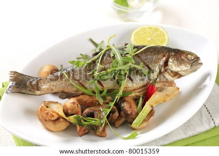 Pan fried trout served with button mushrooms - stock photo