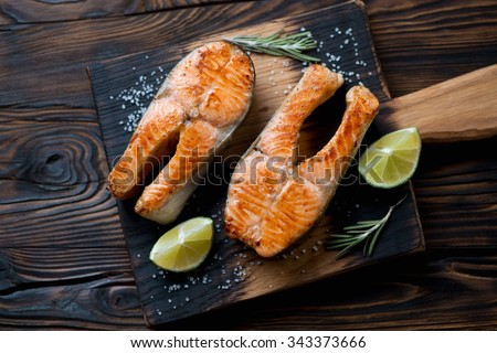 Pan fried trout steaks served on a rustic wooden cutting board, above view - stock photo